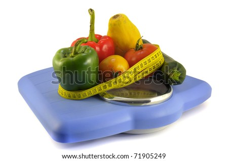 Fruits and vegetables in a weight scale with measuring tape isolate in white