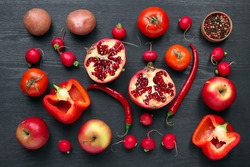 fruits and vegetables red flower scattered on black wooden background