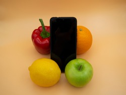 Fruits and vegetables with a mobile phone on the background of a gold fortune. Red pepper, green Apple, yellow lemon, orange grapefruit.
