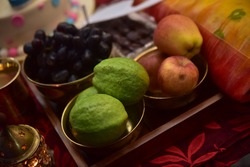 Fruits and yellow saree kept in copper vessel in red background with shallow depth of field