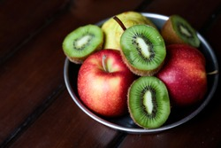 Fruits apple pear and kiwi in metal bowl close up on wooden table with copy space. healthy lifestyle and eating concept. summer vitamins snacks