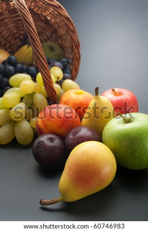 Fruits. Fresh ripe fruits scattered from wicker basket on gray gradient background