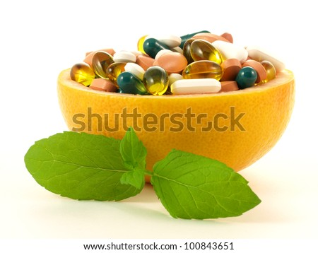 Fruits full of vitamin pills on isolated background.