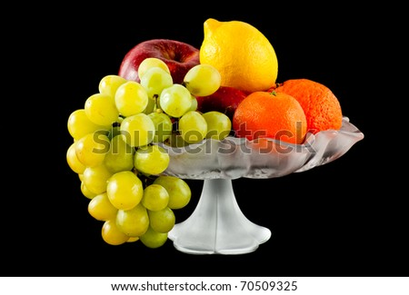 Fruits in glass vase isolated on black