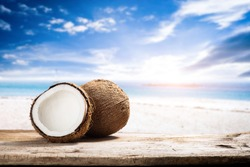 Fruits of coconuts on wooden desk space with beach side blue sky summer.
