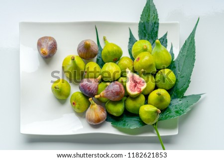 Fruits of fig tree with leaves on white background/ Fresh figs with leaves on rustic table/ Healthy lifestyle concept / Healthy food concept  Stock foto ©