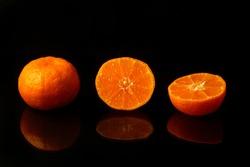 Fruits of mandarin orange whole and cut on black background reflection