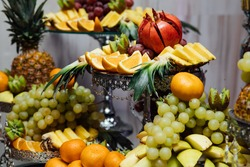Fruits on wedding table at restaurant. Composition of colored fruit, close-up. Decoration with fruit for child birthday. Sweet table with fruit, wedding catering, fruit bar on party