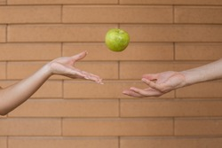 Fruits, organic food, healthy eating and people concept - Close up of the man's hand tossing the green apple while the woman's palm catches it on brick wall background