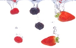 Fruits plunging into water. Strawberry, blackberry and raspberry splashing into fresh water.