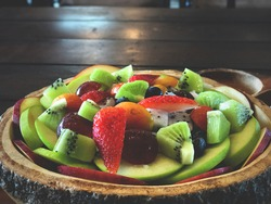 Fruits salad in wooden tray and salad dressing on wooden tray with dark natural light. Smart eating. Diet concept. Muticolor fruits.