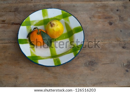 fruits tangerine and pear in vintage porcelain dish plate on retro wood table