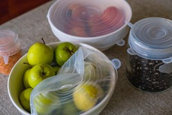 Fruits, vegetables and grains packed with environmentally safe round silicone stretch lids ready for storage. Reusable eco-friendly kitchen products. Zero waste and sustainable plastic free lifestyle