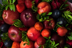 fruity bouquet of red apples with plums, red pepper, strawberry and pistachio branches. On a wooden table and gray background.