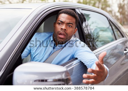 Frustrated African American male driver in car