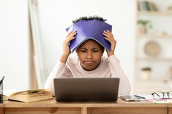 Frustrated African Kid At Laptop Getting Bad Grade During Online Class, Covering Head With Exercise-Book Sitting At Home. School Failure