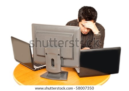 frustrated and stressed young businessman with two laptops and a PC in front of him