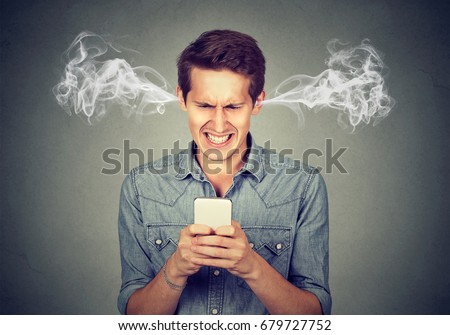 Frustrated angry man reading a text message on his smartphone blowing steam coming out of ears  #679727752