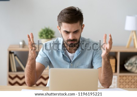 Frustrated annoying man sitting at the desk in office using computer, looking at broken crashed laptop feels anger and indignance. Worried male has verification password problems or data loss concept