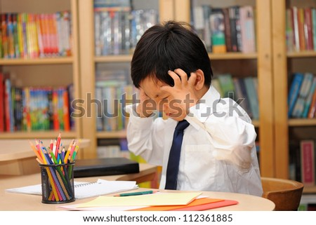 Frustrated Asian schoolboy in school uniform ( white shirt and tie ) doing homework