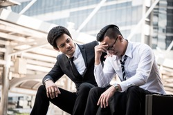 Frustrated Asian young business man sitting outdoor office after he had failed in new project, his colleagues tried to reassure his.