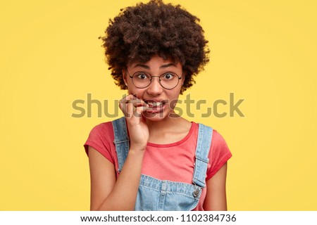 Frustrated beautiful African American female feels anxious and surprised, bites finger nails in puzzlement, looks nervously at camera, worries before presenting project work in front of audience
