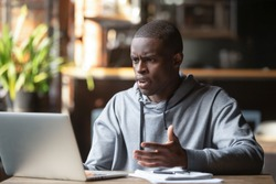Frustrated black male student work at laptop get mad having device software operational problems, angry african American guy man feel confused with slow internet connection on computer or virus attack