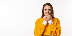 Frustrated brunette girl in casual clothes is covering mouth with two hands not willing to disclose something important. Keep a secret. Studio shot, white background. Mock up copy space