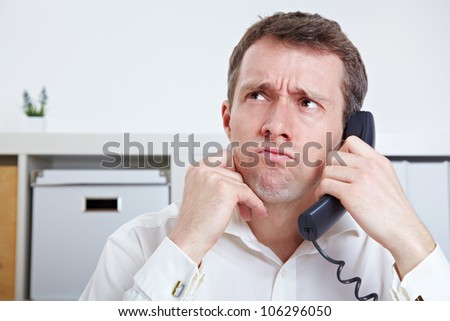 Frustrated business man on the phone in waiting queue