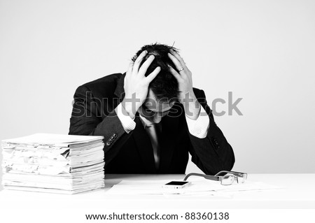Frustrated business man with a pile of bills on his desk