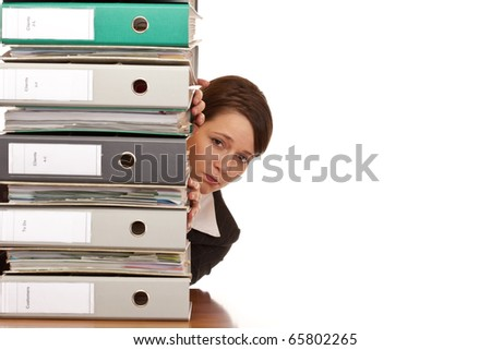 Frustrated business woman looks behind behind a folder stack. Isolated on white background.