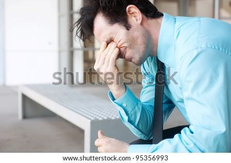 Frustrated businessman sitting on a bench