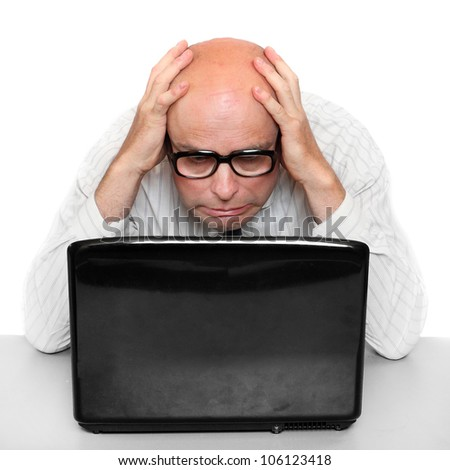 Frustrated businessman with laptop on a desk in the office.