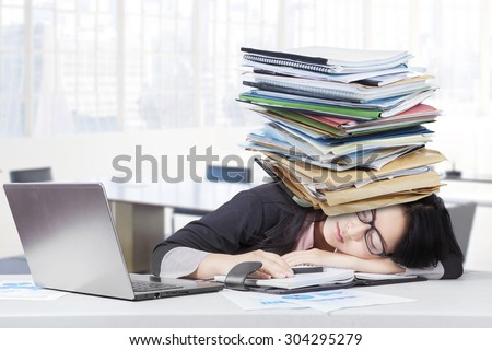 Frustrated businesswoman sleeping in the office with paperwork on head and laptop on the table