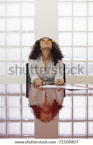 Frustrated caucasian businesswoman holding pencil between mouth and nose in office meeting room. Vertical shape, front view, waist up, copy space