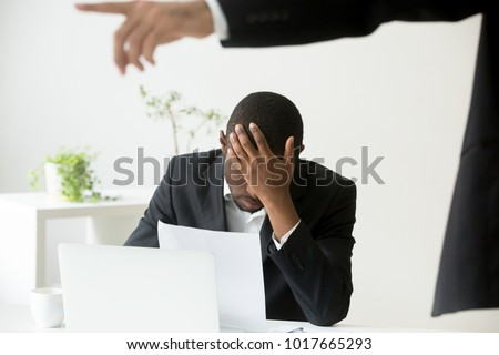 Frustrated despondent african american office worker getting fired from job concept, white boss dismissing depressed sad terminated black employee holding notice, unfair racial discrimination at work