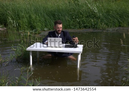 Frustrated, displeased young bearded man, guy. Trying to focus on work. tired of office work. Sitting at a table standing in a swamp in the water