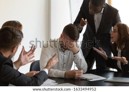 Frustrated employee cover face with hand feels unhappy having serious problems suffers from hostile co-workers, feels guilty, unfair attitude, harassment, stress, discrimination at workplace concept Photo stock ©