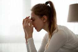 Frustrated female manage emotions feeling broken after hearing bad news, upset girl sit with eyes closed cope with anxiety or depression, hurt heartbroken woman stressed after breaking up or split