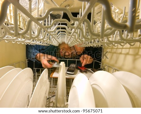 Frustrated grimacing service technician trying to fix a dish washer. Horizontal picture from inside the machine.