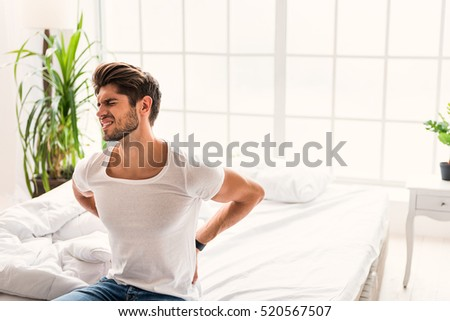 Frustrated guy feels pain in back