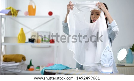 Frustrated housewife looks at blouse hole burned with iron housekeeping problem #1492499681