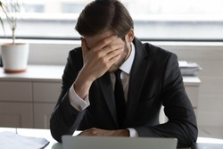 Frustrated male employee sit at desk work on laptop feel stressed with company bankruptcy news, disappointed businessman distressed disappointed with corporate business failure or money loss