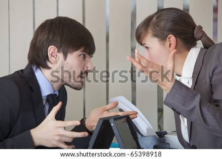 frustrated man and woman discussing by the work in office