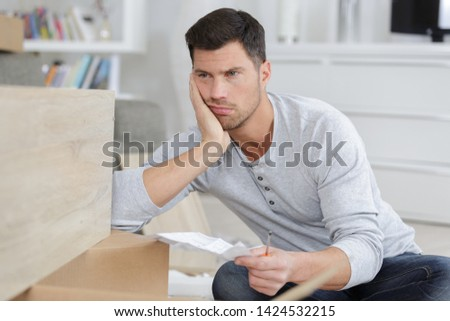 frustrated man holding instructions for assembling furniture