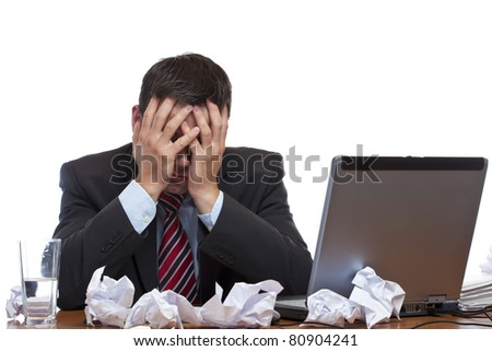 Frustrated man sitting desperate over paper work at desk. Isolated on white background.