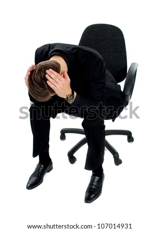 Frustrated man sitting on chair with hands on his head