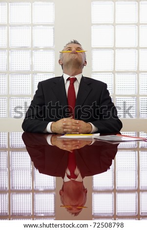 Frustrated mature businessman holding pencil between mouth and nose in office meeting room. Vertical shape, front view, waist up