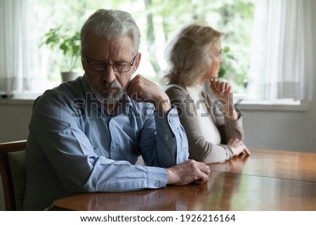 Frustrated middle aged family couple ignoring each other after arguing. Quiet annoyed elder husband and wife sitting separately, going through quarrel, conflict, bad marriage or relationship problem. Stock photo ©