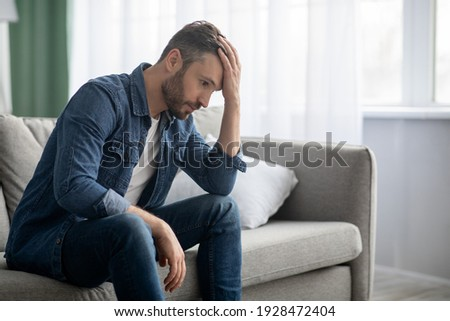 Frustrated middle-aged man sitting on sofa in living room, touching his forehead, having financial troubles during quarantine or suffering from loneliness, copy space, home interior